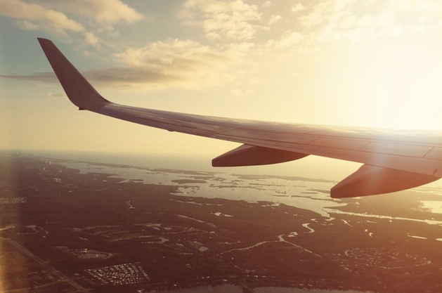 Image of an airplane wing and the sunset