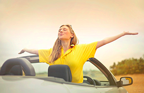 Woman enjoying convertible car ride in the summer time